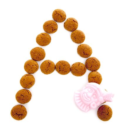 dutch typical: Ginger nuts, pepernoten, in the shape of letter A isolated on white background. Typical Dutch candy for Sinterklaas event in december