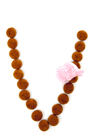 sinterklaas: Ginger nuts, pepernoten, in the shape of letter V isolated on white background. Typical Dutch candy for Sinterklaas event in december Stock Photo