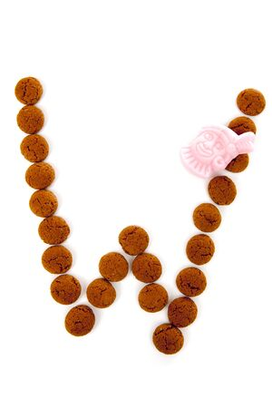 dutch typical: Ginger nuts, pepernoten, in the shape of letter W isolated on white background. Typical Dutch candy for Sinterklaas event in december