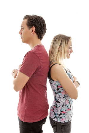 Young couple standing back to back isoalted on white bakground mad at each other Stock Photo