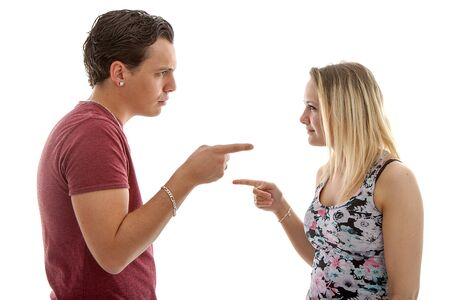 Couple is arguing over white background pointing at each other