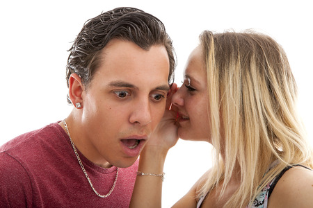 girl is whispering in ear of boyfriend isolated on white background nad he is startled