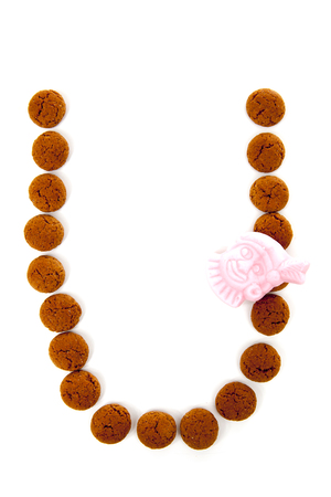 Ginger nuts, pepernoten, in the shape of letter U isolated on white background. Typical Dutch candy for Sinterklaas event in december Stock Photo