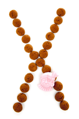Ginger nuts, pepernoten, in the shape of letter X isolated on white background. Typical Dutch candy for Sinterklaas event in december