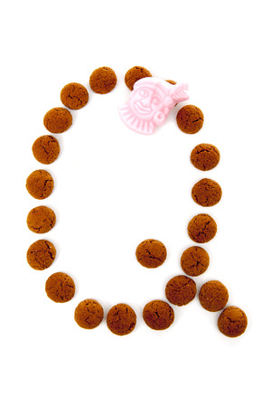 Ginger nuts, pepernoten, in the shape of letter Q isolated on white background. Typical Dutch candy for Sinterklaas event in december