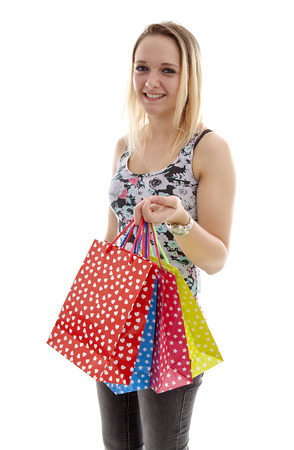 Young acctractive blonde girl is shopping with colorful bags over white background