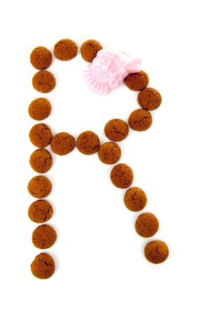 Ginger nuts, pepernoten, in the shape of letter R isolated on white background. Typical Dutch candy for Sinterklaas event in december
