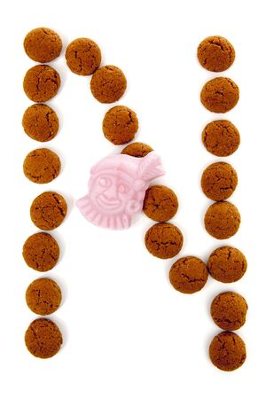 Ginger nuts, pepernoten, in the shape of letter N isolated on white background. Typical Dutch candy for Sinterklaas event in december