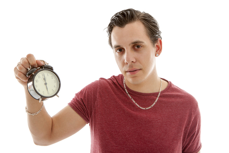 Young man is holding alarm clock at 6 oclock over white background Stock Photo