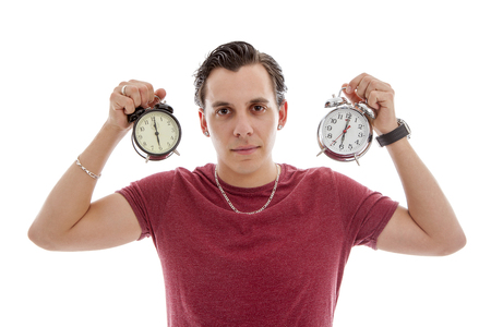 o'clock: Young man is holding two alarm clocks at 6 oclock over white background Stock Photo