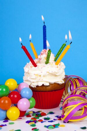 Birthday cupcake with lots of candles, party streamers and colorful confetti over blue background