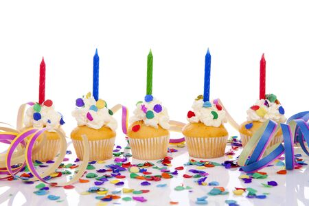 Birthday cupcakes in a row with colorful confetti over white background Stock Photo