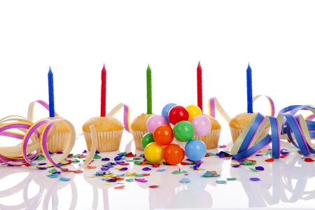 velitas de cumpleaños: magdalenas del cumpleaños en una fila con confeti de colores y globos sobre fondo blanco Foto de archivo