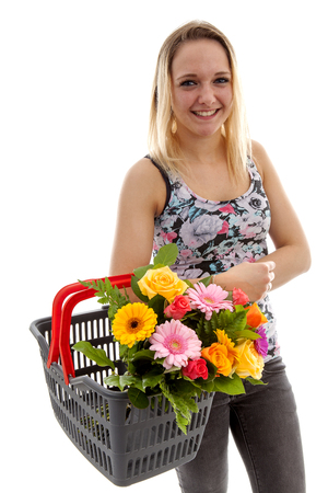 Young woman is holding basket with bouquet of colorful flowers over white background