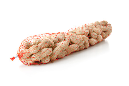Peanuts in net for bird food over white background