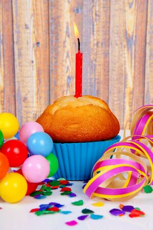 Birthday cupcake with candle and colorful confetti over wooden background