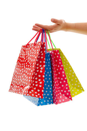 Hand is holding colorful shopping bags over white background
