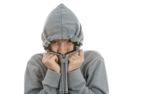 Boy is hiding in his hoodie over white background Stock Photo