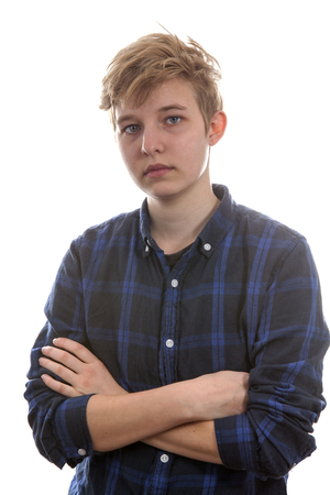 Teenage transgender boy is looking angry. Posing over white background