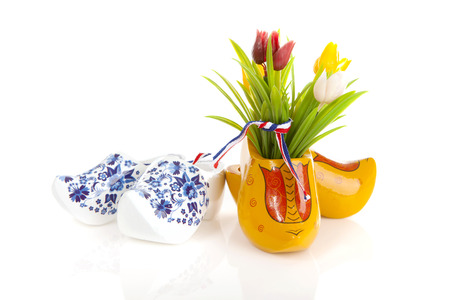 Pair of typical Dutch wooden shoes with tulips over white background Фото со стока