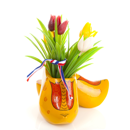 Pair of typical Dutch wooden shoes with tulips over white background Stock Photo