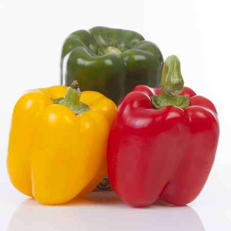 Three colorful bell peppers in green, yellow and red over white background