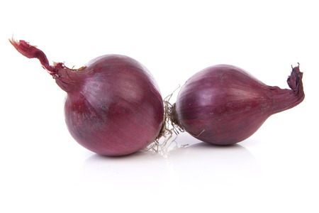 Two raw red onions over white background