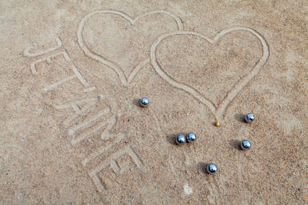 Bocce balls in sand with signed hearts and text I love you in French