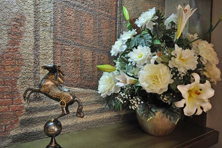 Still Life - a souvenir statuette of the horse and vase with white flowers photo