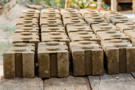Raw bricks covered with sawdust drying in the open air.