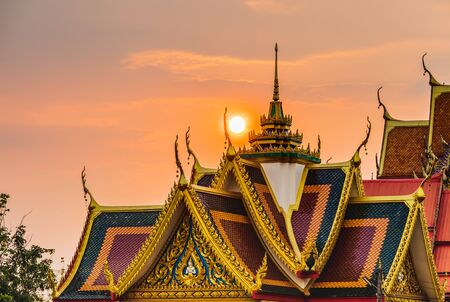 Beautiful thai temple roof detail with colorful architectural work  temple with thailand and lovely sun beam in the background.