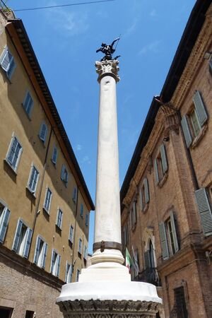 Ancient roman slender column, topped with a bronze sculpture of St. George Slaying the Dragon, Urbino, Marche, Italy Stock Photo