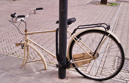 padlocked: Bicycle without a wheel padlocked to a pole