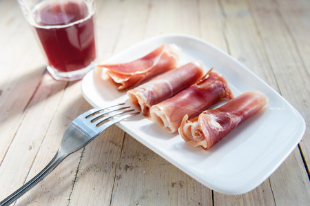 plate of cured ham on wooden background photo