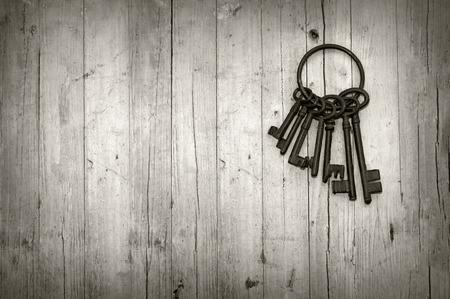 puerta abierta: manojo de llaves viejas en fondo de madera blanco y negro Foto de archivo