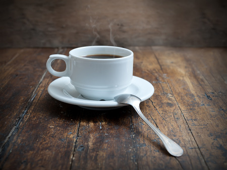 coffee cup with metal spoon isolated on rustic background photo
