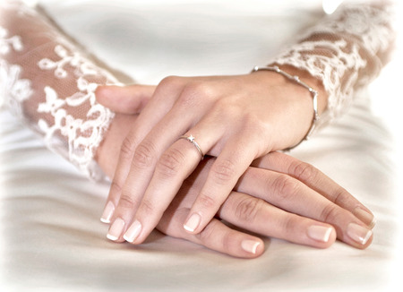 manos: hands clasped showing a wedding ring on her finger