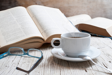 cup of coffee on rustic wooden table with open books photo