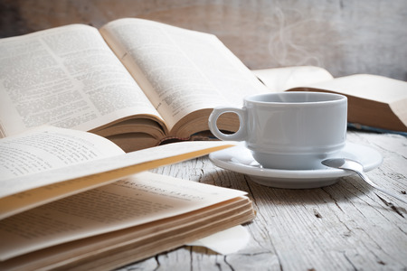 cup of coffee on rustic wooden table with open books Stock Photo