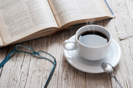 decaffeinated: cup of coffee on rustic wooden table with open books Stock Photo