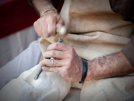 craftsman: artesano que trabajaba en la piedra aislada en manos Foto de archivo