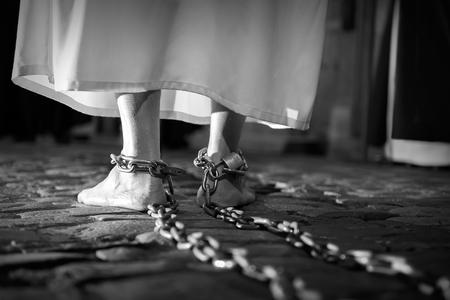 shackled: penitente con los pies encadenados y descalzos en el suelo Foto de archivo