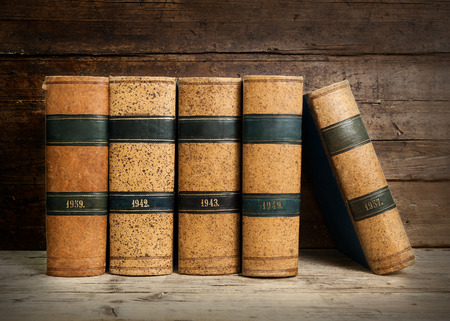 time bound: old bound books on vintage wooden background