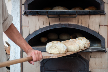 introducing: introducing baker bread dough in the oven of wood