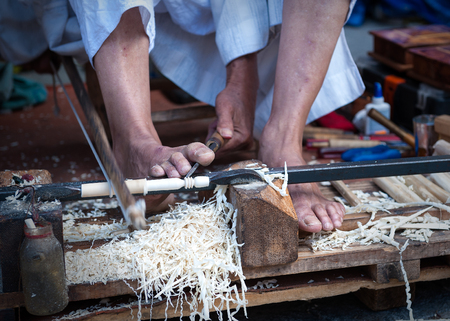 gouge: craftsman using his feet to carve wood