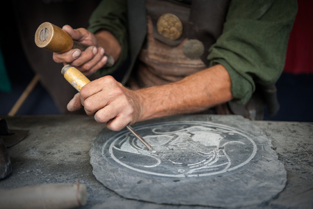 wood stone: Craftsman hands working on a slate plate Stock Photo
