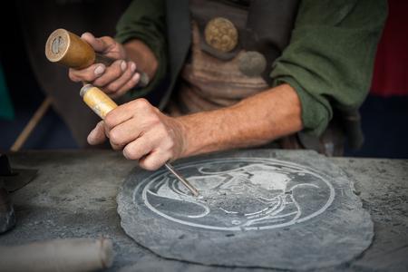 medieval: Manos del artesano que trabaja en una placa de pizarra