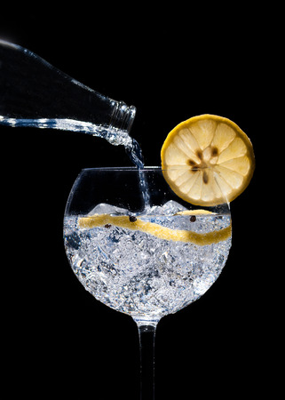glass of gin and tonic on black background