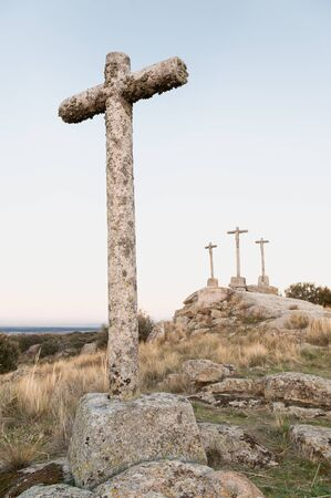 atonement: Three Crosses of carved stone on granite rock at dusk of Heaven