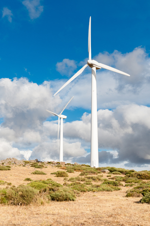 various mountain wind turbine with green grass and cloudy sky
